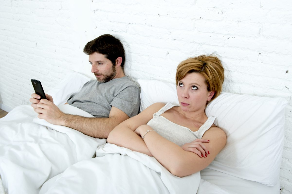 A husband is on his phone with a lover while his wife is in bed, showing the need for Chicago divorce attorneys.