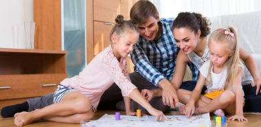 Happy young parents and two little daughters playing a board game at home represent how Lake Forest family law attorneys can help.