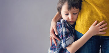 A sad little boy hugging his mother and not wanting to leave with his father represents how a Chicago child custody attorney can help you keep your children.