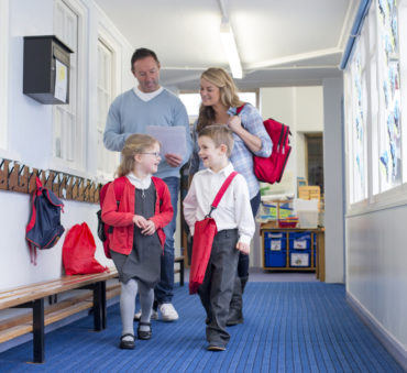 Parents and students walking down a primary school hallway represent how parents can get along after a divorce with the help of a Chicago divorce attorney.