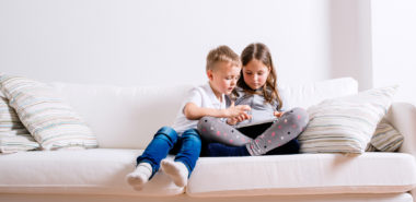 A little girl and boy sit on a sofa with a tablet looking at their mother's Chicago divorce attorneys' website.