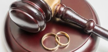 This is a closeup view of a gavel and wedding rings representing how a Chicago family law attorney can help obtain a divorce.