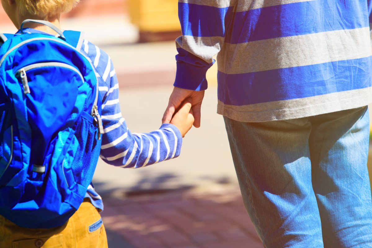 A father holding the hand of his little son while going to school represents how a Chicago child custody attorney can help you get support from the other parent.