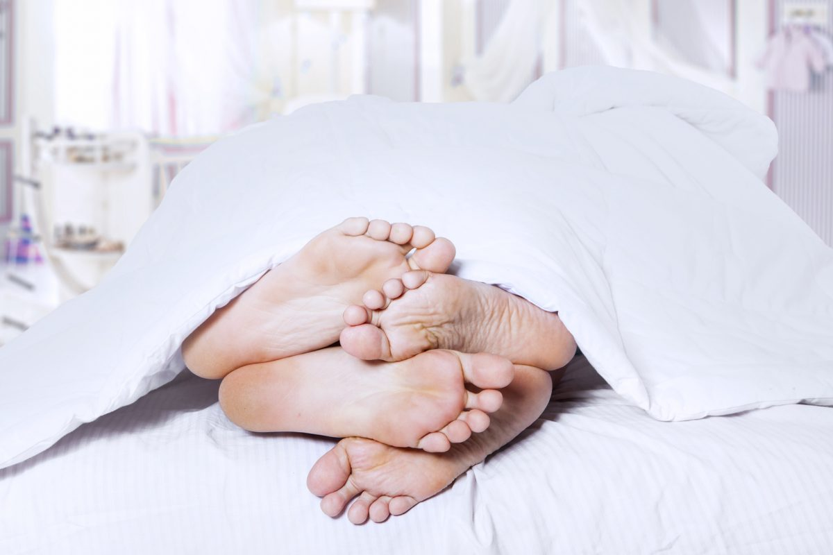 This close-up of a couple's feet cuddling represents an affair and why one would need a Lake Forest divorce attorney.