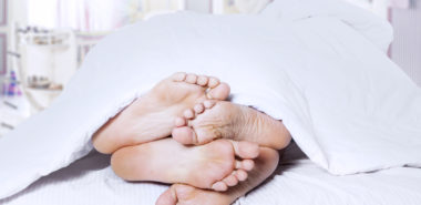 Close-up of couple's feet cuddling representing an affair and why one would need a Lake Forest divorce attorney.