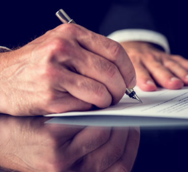 Closeup of male hand signing a power of attorney document with a Lake Forest divorce attorney.
