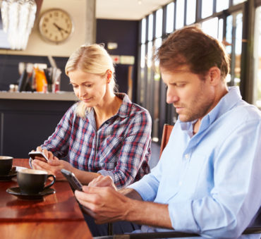 A man and woman use smart phones at a coffee shop, looking for a Lake Forest divorce attorney.