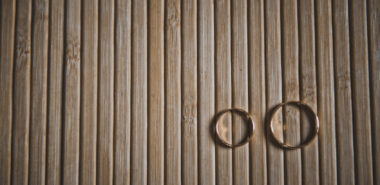 Two wedding rings sit on a wooden table after their owners met with a Chicago divorce attorney.