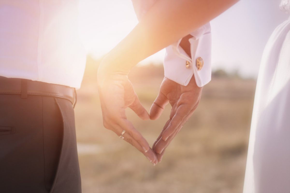 A bride and groom hold hands after discussing prenuptial agreements with a Chicago divorce attorney.