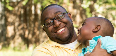 A father and son smile after a paternity test ordered by a Chicago family law attorney.