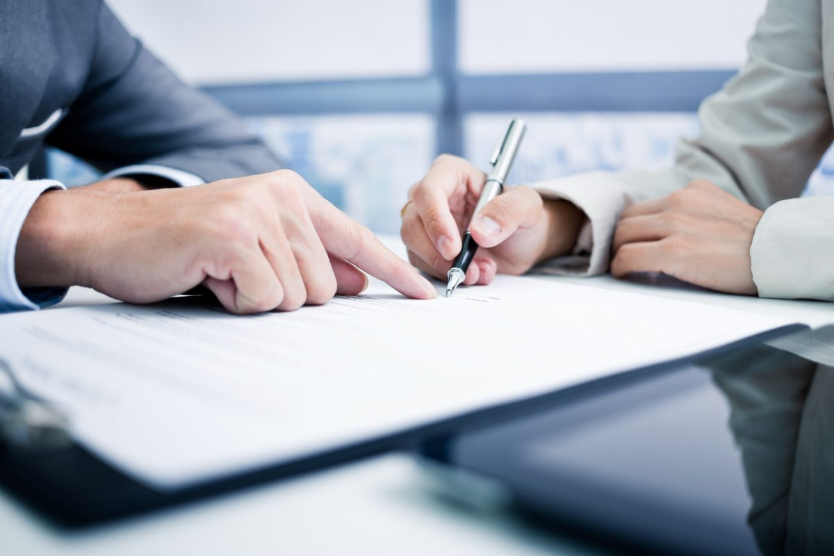 A woman signs a divorce agreement with help from her Chicago divorce attorney.