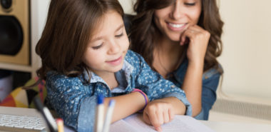 This is a concept of a mother helping her little child with homework representing how a Chicago custody attorney can help you keep your child.