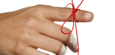 Image of a hand tied with a red rope representing the need to contact Chicago divorce lawyers best