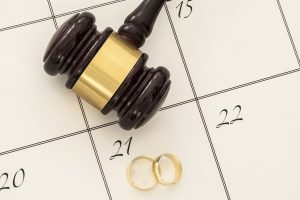 Divorce concept with gavel and wedding rings on a calendar for a divorce attorney chicago