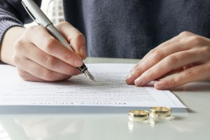 Wife signs divorce decree form with ring after talking with a divorce lawyer naperville
