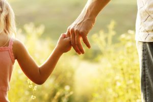 a parent holds the hand of a small child for a chicago family law lawyer