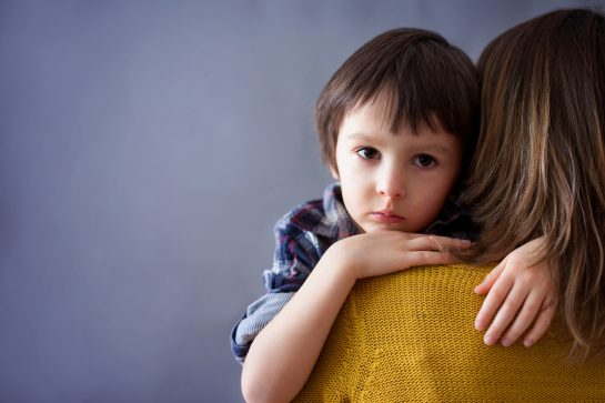 Sad little child, boy, hugging his mother at home who is about to call a top parental alienation lawyer in chicago
