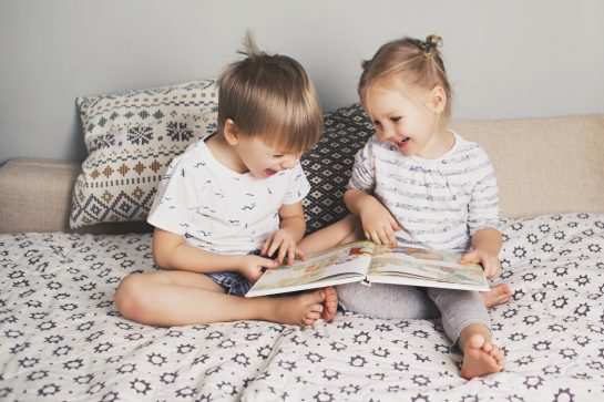 Two kids sitting on bed and reading a book
