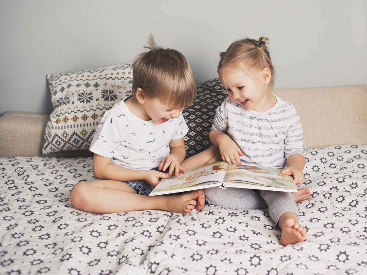 Two kids sitting on bed and reading a book, hygge