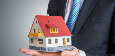 Real estate agent is holding small house in hand.