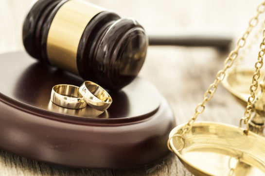 A gavel with wedding rings representing how if you are going through a divorce, our Chicago divorce attorneys can assist you