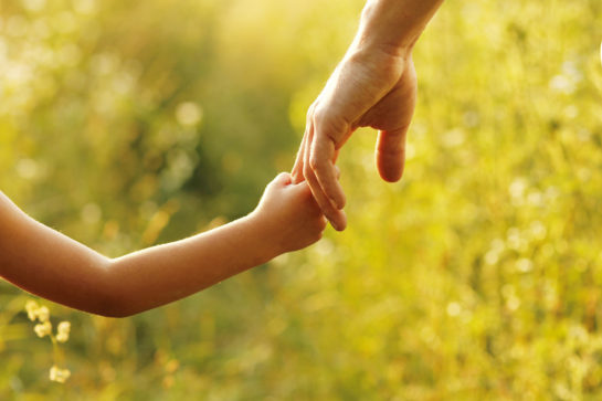 A parent holding a child's hand representing how our Oak Park divorce attorneys can assist you with child custody matters