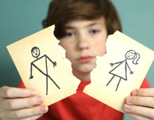 Sad boy with drawings of mom and dad ripped apart representing how our Highland Park child custody lawyers can assist you with your custody case