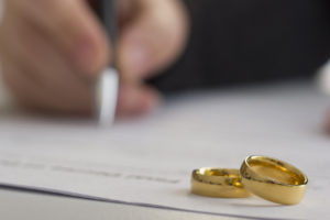 Hands signing divorce papers with wedding rings on the table representing how our Bolingbrook attorneys can help you with your divorce case