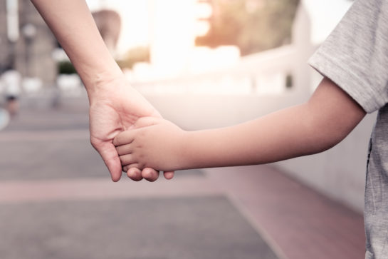 Child holding the hand of a parent representing how our Naperville child custody lawyers can help you with your custody and divorce case