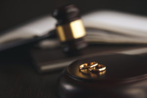 Wedding rings with a gavel representing how our Chicago divorce lawyers can assist you with the divorce process