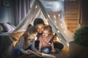 mom with daughters reading in a tent representing how our Chicago family law attorneys can help you with all aspects of family law