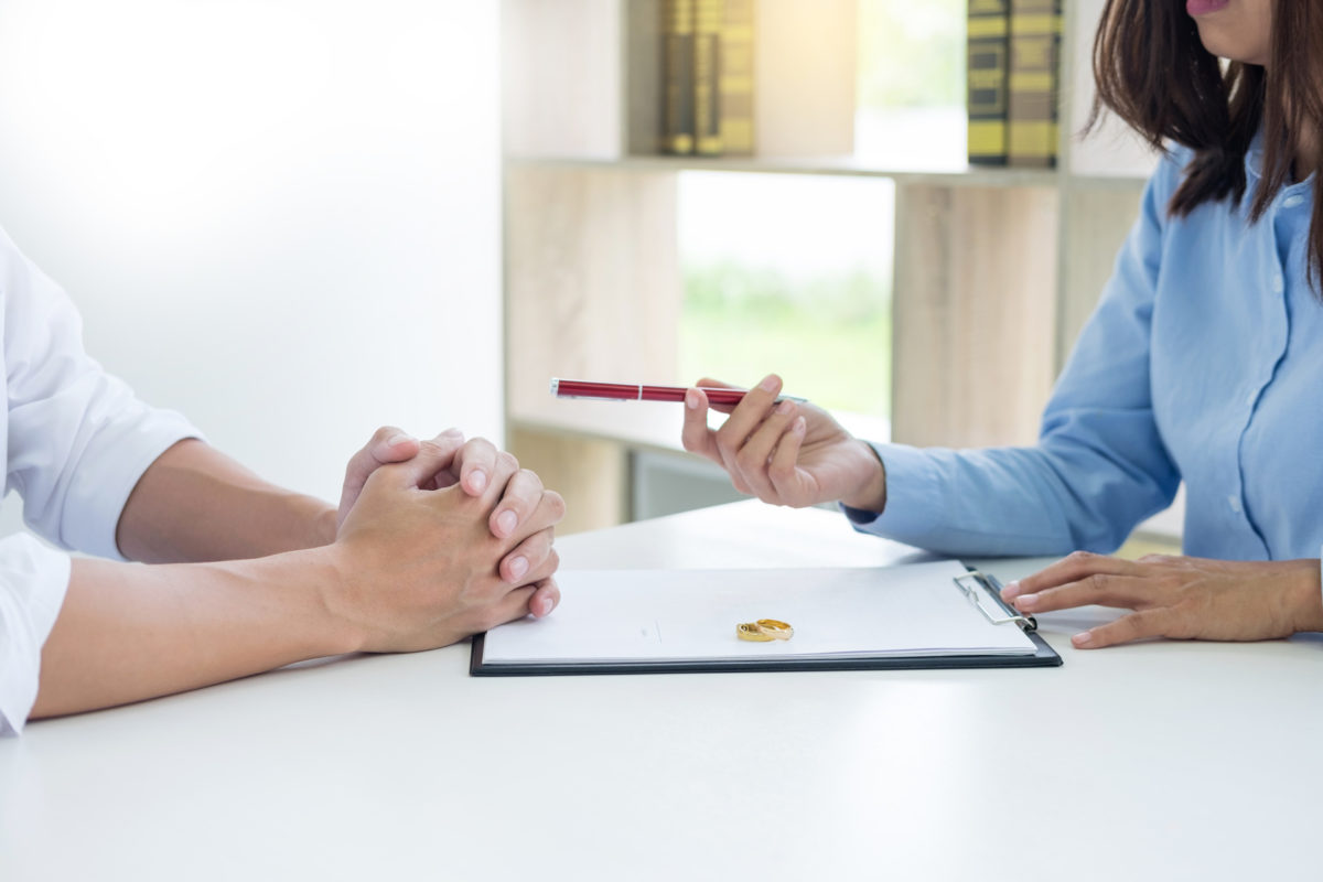 Couple signing divorce papers representing how our Chicago divorce lawyers can help you if you're considering divorce