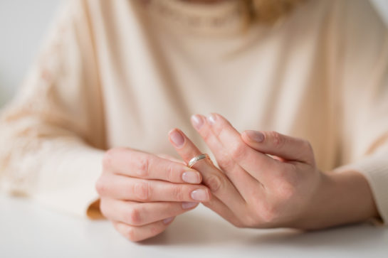 woman taking off wedding ring representing how our Chicago divorce attorneys can help you with your divorce case