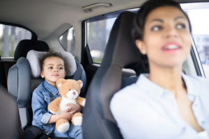 A mother with her daughter driving in car in need of a good Child custody lawyer near me.