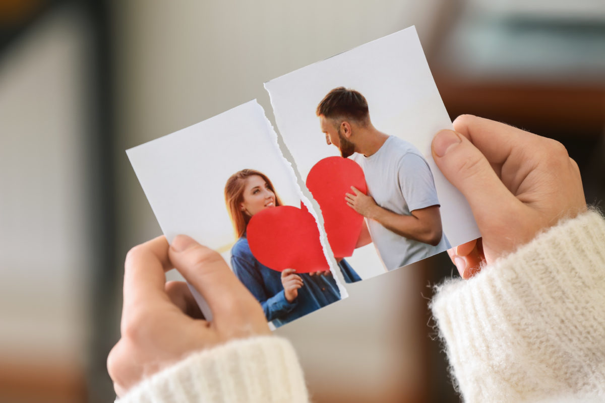 Woman tearing up a photo of couple, if considering divorce meet with a Chicago Loop separation attorney.