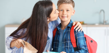 Mother handing her son his school lunch and kissing his cheek, for the best Chicago child custody attorney call our office.