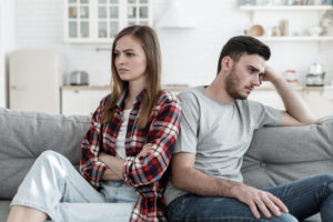Man and woman sitting on couch back to back representing breakup. For help with your spousal support speak to Divorce Lawyers Near Me.