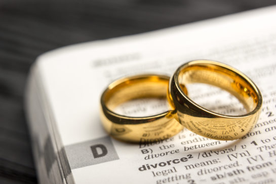 Two wedding rings laying on dictionary definition of divorce, realize you need help with your divorce proceedings with good Northbrook Divorce Lawyers.