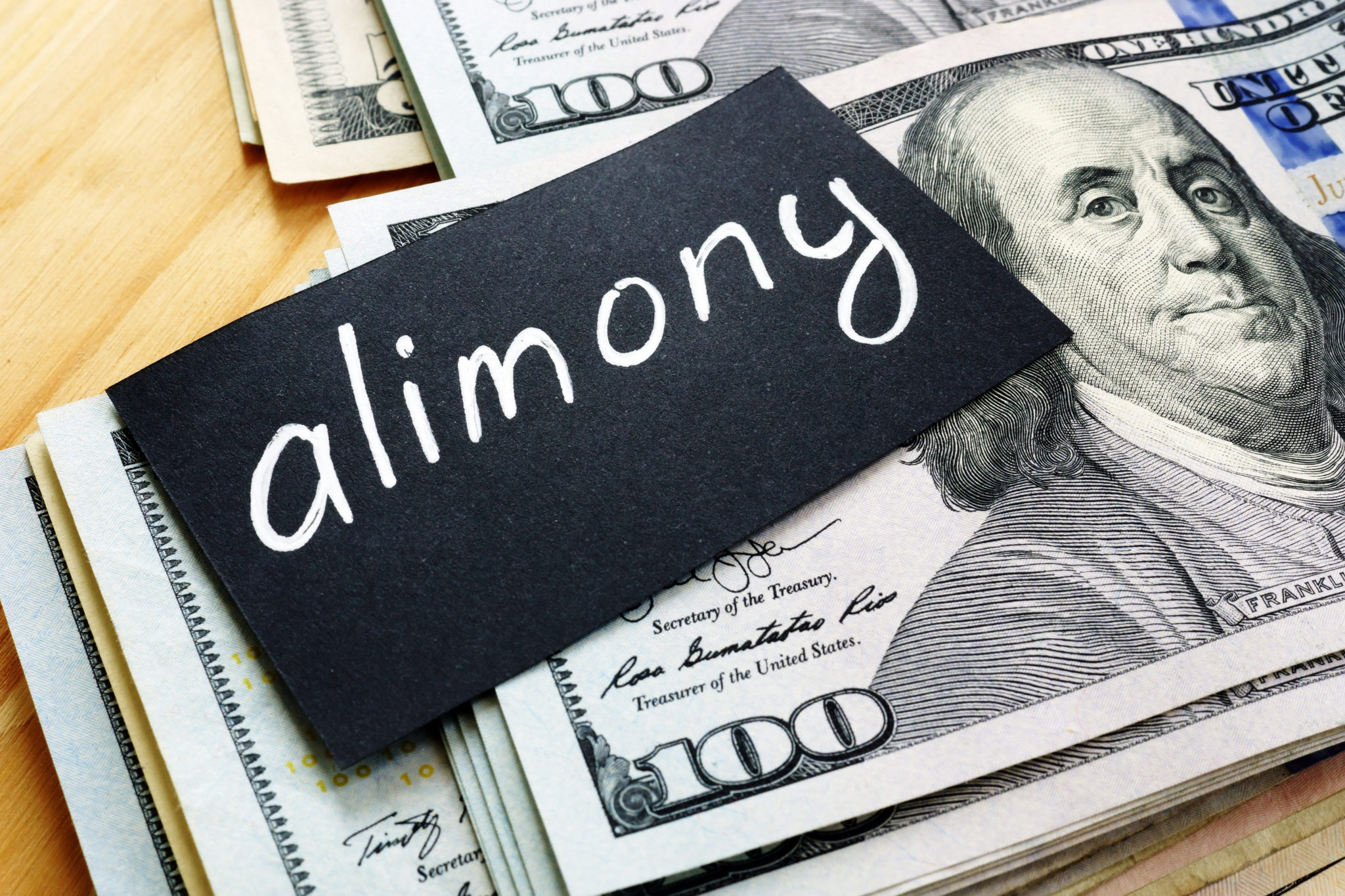 Alimony sign on a stack of hundred dollar bills, for determining amount for spousal support talk to Chicago Alimony Attorneys.