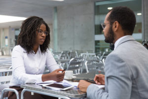 Lawyer with female client sitting at a table with a lot of paper talking, representing how one can benefit from contacting a Lake County divorce lawyer.