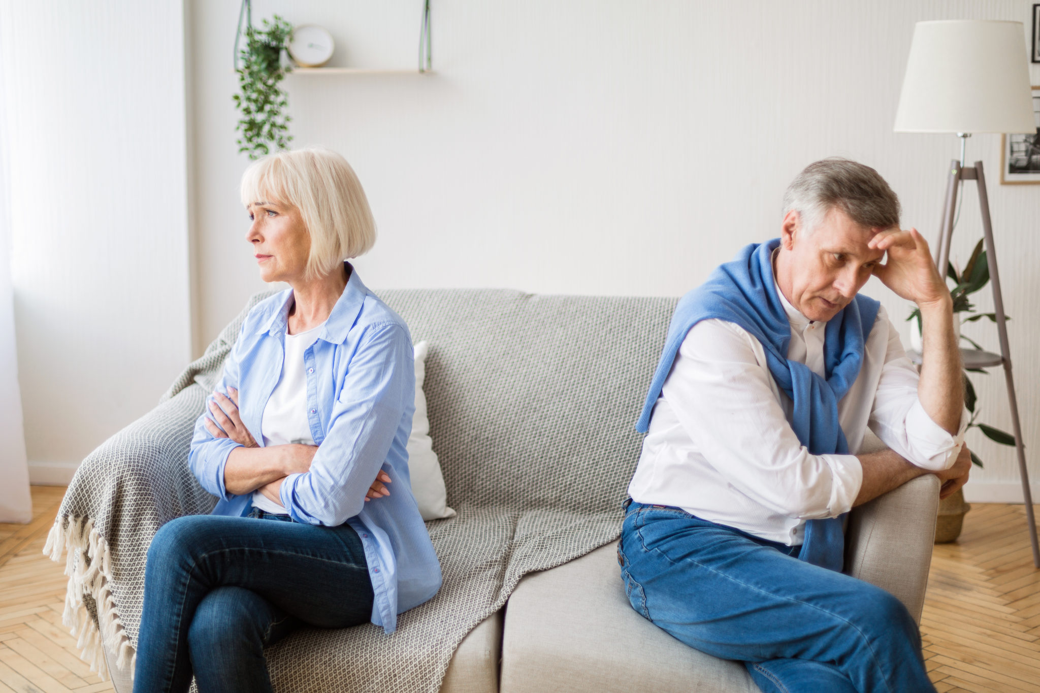 An older couple sitting on a couch looking at opposite directions, representing how one can benefit from calling a Chicago divorce lawyer.