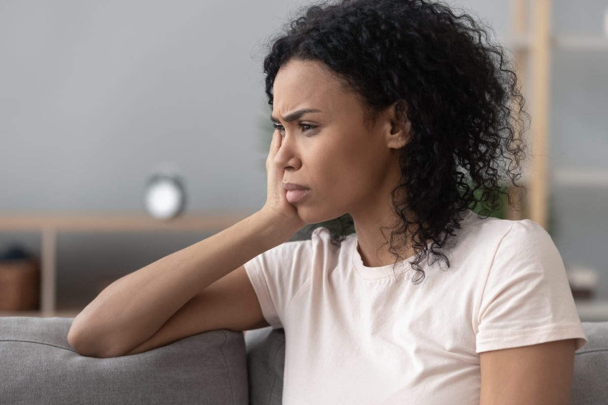 A women sitting on a gray couch looking worried, representing how one can benefit from calling a Chicago divorce lawyer.
