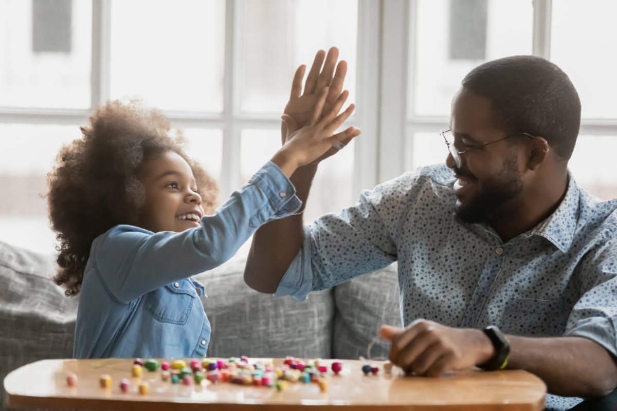 A father and daughter playing a board game and high fiving each other with big smiles, representing how one can benefit from calling a Chicago child support lawyer.