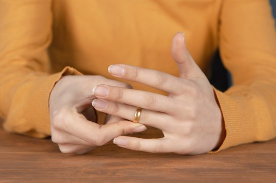 A woman wearing a yellow shirt resting her hands on a table removing her wedding ring. Representing how one can benefit from calling an Oak Brook's divorce lawyer.