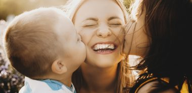 A woman smiling getting kisses by her children, representing how one can benefit from calling a Chicago divorce attorney.