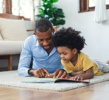 A father and son laying on a carpet looking at a book, representing how one can benefit from calling a Chicago paternity lawyer.