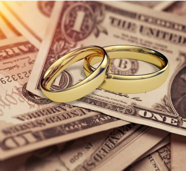 Two wedding rings lay on top of money representing how a Chicago divorce attorney can assist you with your case.
