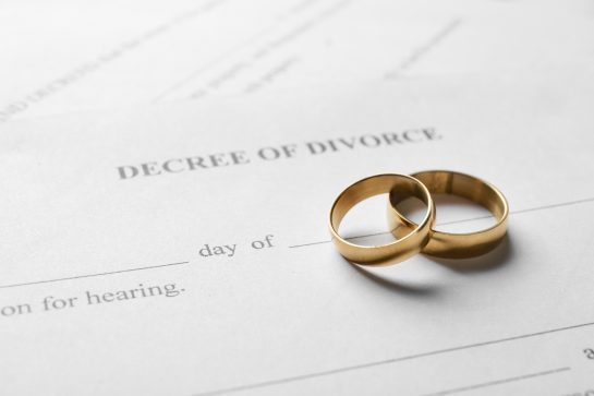 Close up of two wedding rings sitting on top of a divorce decree. Let the best Chicago divorce lawyers at our firm represent you.