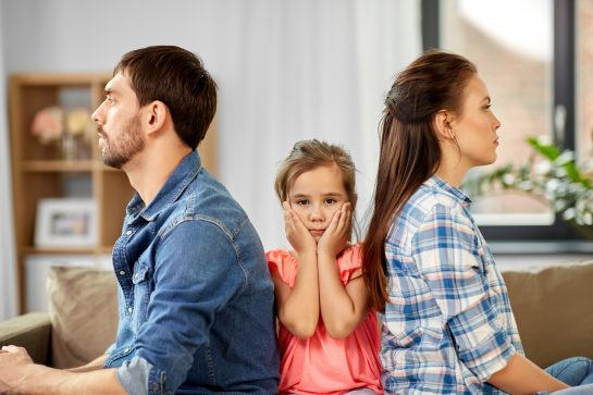 A distressed child sitting between their parents, representing how our Wheaton child custody attorneys can represent you in your child custody case.