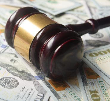 Gavel lays on top of money representing how a Chicago child support attorney can assist you with your case.